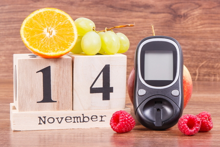 Date of 14 November on cube calendar, glucometer and fresh ripe fruits, concept of world diabetes day