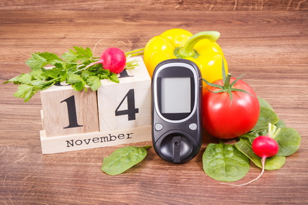 Date 14 November on cube calendar, glucometer for checking sugar level and fresh vegetables, world diabetes day and fighting disease concept