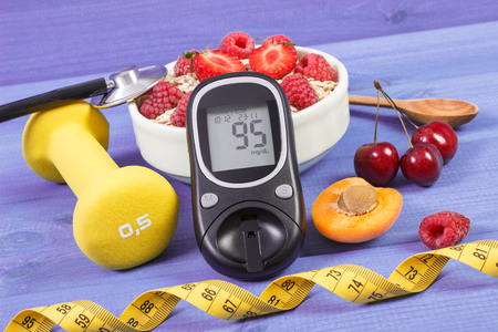 glucose: Glucometer with result of sugar level, oat flakes with fruits, tape measure and dumbbells for fitness, concept of diabetes, slimming, sporty and healthy lifestyles Stock Photo