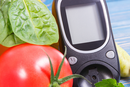 Date 14 November as symbol of world diabetes day, glucometer for measuring sugar level and fresh vegetables, concept of fighting disease