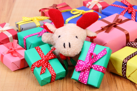 Plush reindeer and heap of wrapped colorful gifts for Christmas, birthday, valentines or other celebration on wooden background Stock Photo