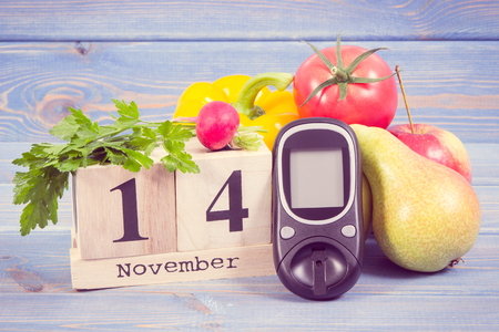 Date of 14 November on cube calendar, glucose meter and fresh ripe fruits with vegetables, concept of world diabetes day Stock Photo