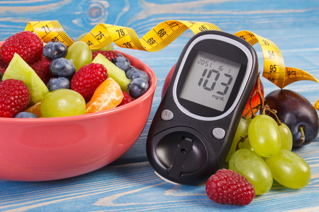 Fresh fruit salad, glucometer with result of sugar level and tape measure, concept of diabetes, diet, slimming, healthy lifestyles and nutrition Imagens