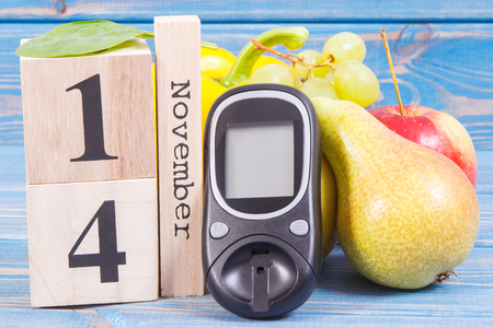 Date 14 November on cube calendar, glucometer for checking sugar level and fresh fruits with vegetables, world diabetes day and fighting disease concept