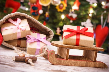 Gifts with ribbon for Christmas on wooden sled and in jute bag on background of christmas tree with lights and decoration