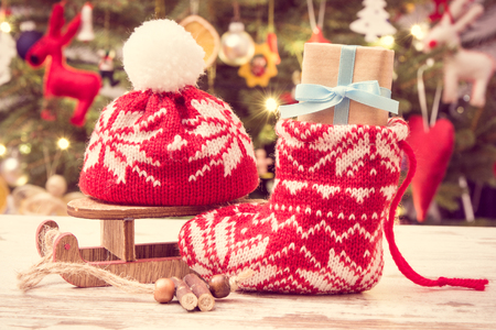Wrapped gift with ribbon for Christmas with woolen red sock and cap on background of christmas tree with lights and decoration