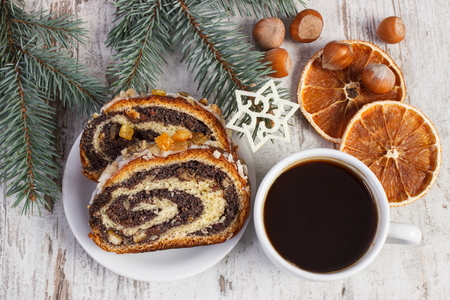 strudel: Poppy seeds cake on plate, coffee and spruce branches, dessert for Christmas, rolled up traditional polish poppy pie Stock Photo