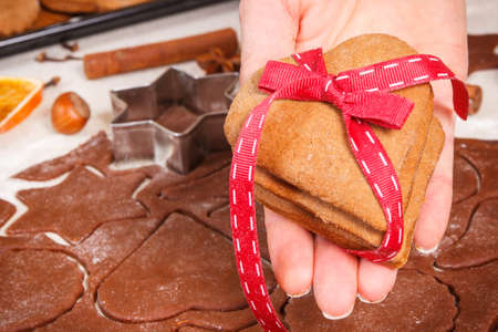 Hand with fresh baked homemade gingerbread or cookies for Christmas time and accessories for baking