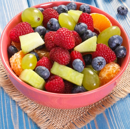 Fruit salad with raspberries, melon, mandarine, grapes and blueberries, concept of diet, slimming, healthy lifestyles and nutrition