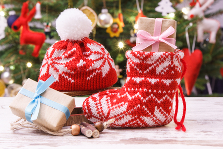 Gift with ribbon for Christmas with woolen red sock and cap, christmas tree with lights and decoration in background, festive time concept