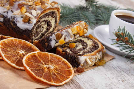 Poppy seeds cake, black coffee and spruce branches on rustic board, dessert and decoration for Christmas time Zdjęcie Seryjne