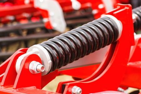 Closeup of steel spring on industrial or agricultural machine, detail and part of hydraulic or pneumatic machinery, engineering and technology Stock Photo