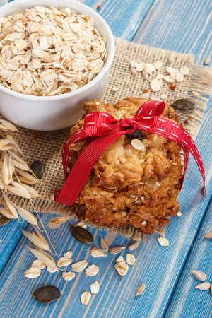 Fresh baked homemade crusty oatmeal cookies with ingredients and ears of oat, concept of delicious healthy dessert