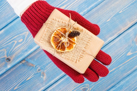 Hand of woman in woolen gloves holding decorated gifts for Christmas, Valentine, birthday or other celebration
