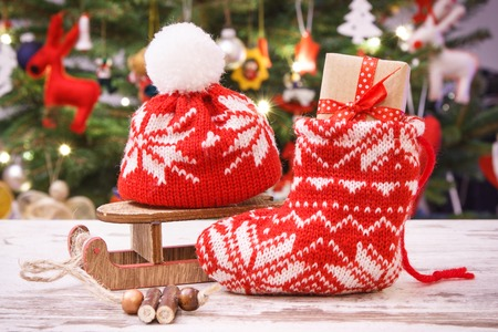 Gift with ribbon for Christmas in red festive sock on background of tree with lights and decoration, Christmas time concept