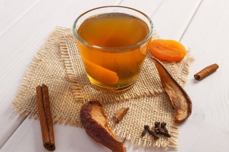 Cup of fresh traditional compote or beverage of dried fruits, ingredients and spices on boards, healthy nutrition