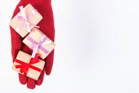 Ruka ženy v červených vlněných rukavicích a zabalené dárky na Vánoce, Valentine, narozeniny nebo jiné oslavy, kopírovat prostor pro text na bílém Reklamní fotografie