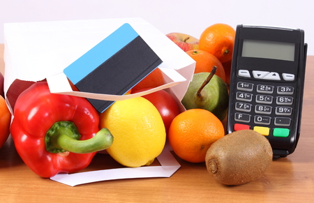 Payment terminal, contactless credit card and paper shopping bag with fruits and vegetables, cashless paying for shopping