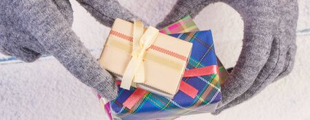 Hands of woman in woolen gloves and wrapped colorful gift for Christmas, Valentine, birthday or other celebration