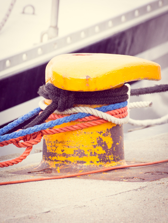 Colorful rope and old yellow mooring bollard in seaport, closeup and detail of yachting