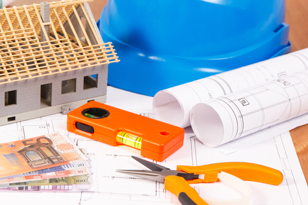 Electrical construction drawings or diagrams, orange work tools for engineer jobs, small house and currencies euro, building home cost concept Stock Photo