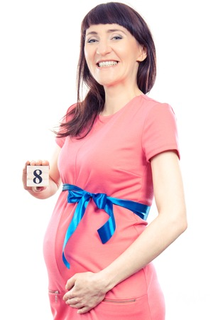 Smiling pregnant woman in pink dress with blue ribbon showing number of eighth month of pregnancy, concept of extending family and expecting for newborn Stock Photo