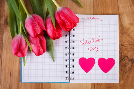 Date of February 14 written in notebook or calendar, fresh tulips and hearts of paper, decoration for Valentines Day
