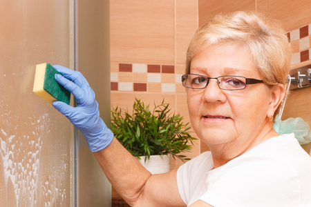 Elderly senior woman in protective rubber gloves using sponge with detergent for cleaning shower glass, concept of household duties