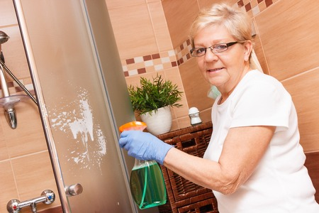 Elderly senior woman in protective rubber gloves using detergent for cleaning shower door, concept of household duties Zdjęcie Seryjne