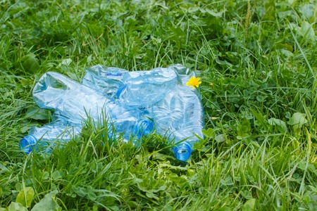 Crushed plastic bottles of mineral water on grass in park, concept of environmental protection, littering of environment concept