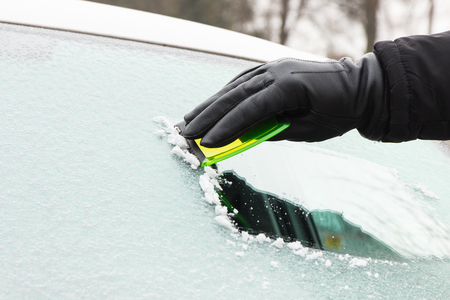 Hand of man in leather glove scraping ice or snow from car windscreen Stock fotó - 96431640