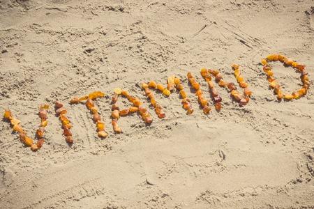 Photo vintage, inscription vitamine D faite de pierres d'ambre sur le sable à la plage, concept de temps de vacances, mode de vie sain et prévention de la carence en vitamine D Banque d'images - 96666306