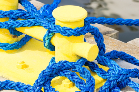 Blue rope and yellow mooring bollard in port, closeup and detail of seaport, yachting concept