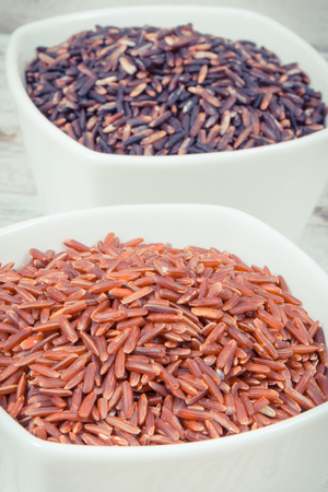 Vintage photo, Black and red rice in white glass bowls on rustic board, concept of healthy, gluten free nutrition Stock Photo