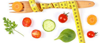 Wooden fork wrapped tape measure and fresh ripe vegetables on white background, concept of slimming and healthy nutrition