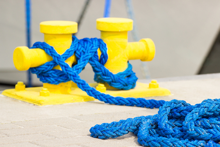 Blue rope and yellow mooring bollard in port, closeup and detail of seaport and yachting Stock Photo