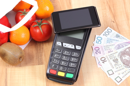 Payment terminal with mobile phone with NFC technology and polish money, fruits and vegetables in shopping bag, choice between cashless and cash paying for shopping