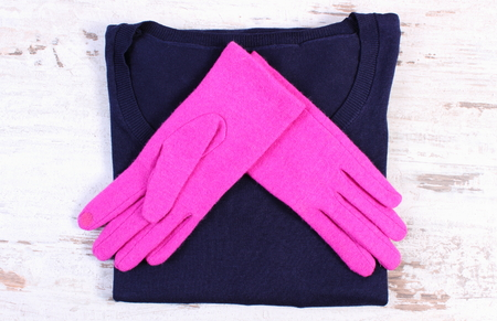 Pair of pink gloves and navy blue sweater for woman on old rustic board, womanly accessories, warm clothing for winter
