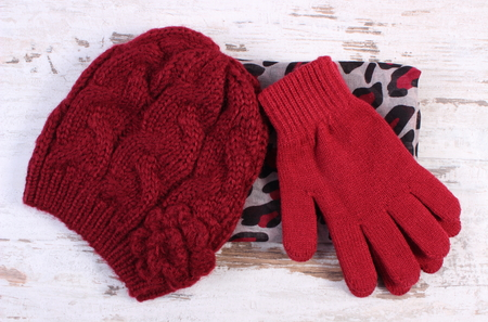Pair of woolen gloves, cap and colorful shawl for woman on old rustic board, womanly accessories, warm clothing for winter