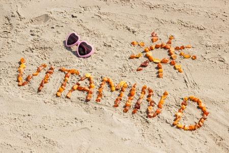 Okulary przeciwsłoneczne, napis witamina D i kształt słońca na piasku na plaży, pojęcie wakacji i profilaktyka niedoboru witaminy D.