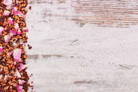 Dried wild rose petals and tea grains on old rustic boards, copy space for text or inscription