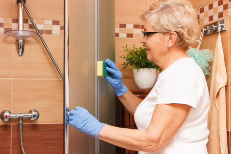 Elderly senior woman in protective gloves wiping shower glass, concept of house cleaning and household duties Zdjęcie Seryjne