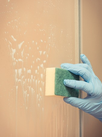 Hand of senior woman in protective gloves washing and cleaning glass shower using detergent and sponge, concept of household duties