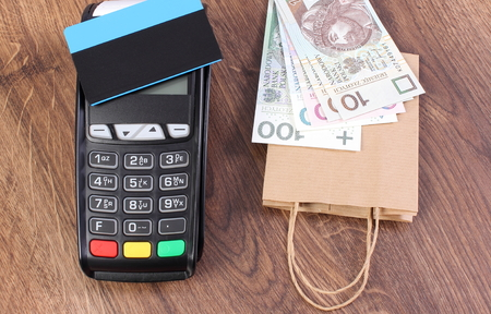 Payment terminal with contactless credit card, polish currency money and paper shopping bag Stock Photo