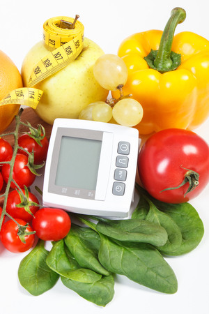 Blood pressure monitor, fresh fruits with vegetables and tape measure, concept of healthy lifestyle, slimming and prevention of hypertension