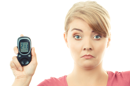 Shocked and worry woman holding glucometer with bad result of measurement sugar level, concept of diabetes and checking sugar level Zdjęcie Seryjne