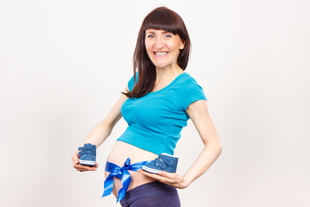 Happy smiling pregnant woman with blue ribbon on belly holding baby shoes, concept of extending family and expecting for newborn boy