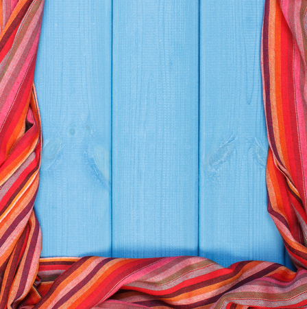 Frame of colorful womanly shawl on boards, warm clothing for autumn or winter, copy space for text