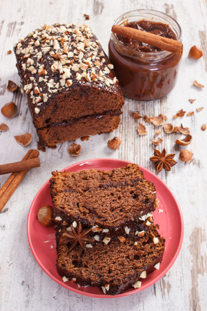 Fresh gingerbread or dark cake with cocoa, chocolate and plum jam on old rustic boards, delicious dessert concept Stock Photo