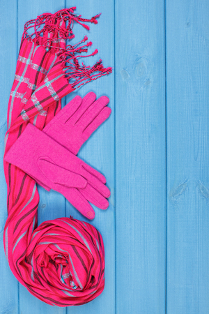 Woolen gloves and shawl for woman on boards, warm clothing for autumn or winter, womanly accessories, place for inscription Stock Photo